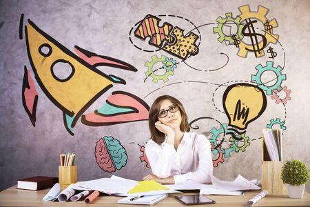 Mujer joven pensativa que sueña despierto en el lugar de trabajo con el bosquejo creativo del cohete. Concepto de emprendimiento Foto de archivo - 77652209