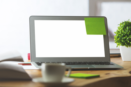 keyboard: Close up of wooden office table with green sticker on white laptop screen, blurry coffee cup, decorative plant and other items. Mock up