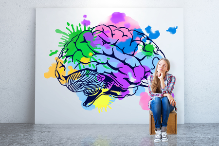 Young woman sitting in concrete room with colorful brain sketch on banner. Creative thinking concept. 3D Rendering