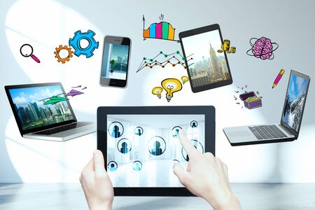 female hands: Female hands holding and pointing at tablet with multiple devices and drawings above. Cloud computing concept Stock Photo
