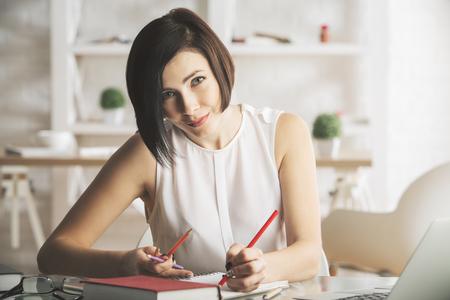 Portrait de jolie jeune femme caucasienne, faire de la paperasse et à l'aide d'ordinateur portable dans le bureau moderne. Elle travaille sur le projet Banque d'images