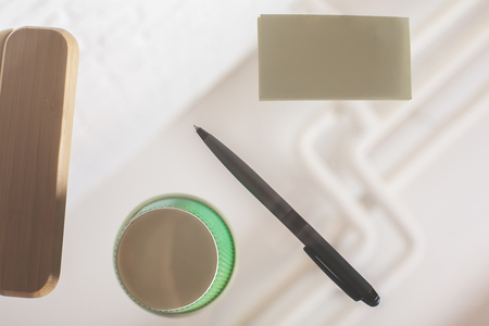 close up food: Bottom view of glass table with coffee cup, pen, empty business card and other items. Mock up Stock Photo