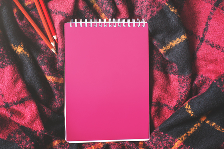 bed sheet: Top view and close up of pink spiral notepad, red checkered plaid and pencils. Mock up