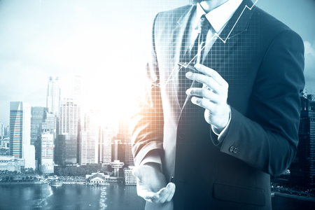 financial growth: Businessman drawing business chart on city background. Financial growth concept
