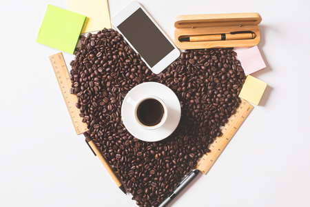 brown: Top view of coffee cup, beans shaped as a heart, supplies and blank smartphone. Morning concept