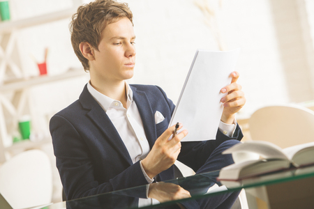 working office: Portrait of handsome young man doing paperwork at workplace Stock Photo