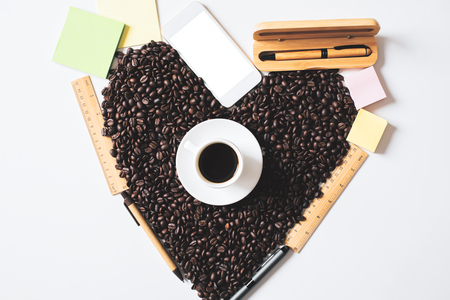 Top view of coffee cup, beans shaped as a heart, supplies and blank white smartphone. Morning concept