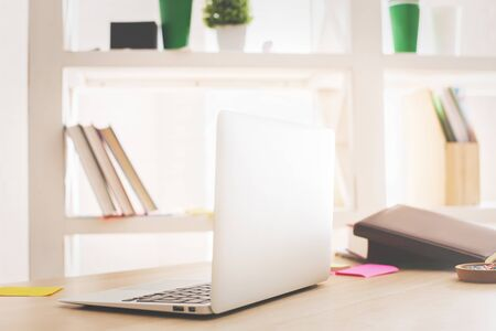 table top: Side view of open laptop placed on wooden office desktop with book, supplies and other items Stock Photo