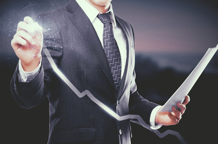 expertise: Young businessman with document in hand drawing digital chart arrow on dark background. Success concept Stock Photo