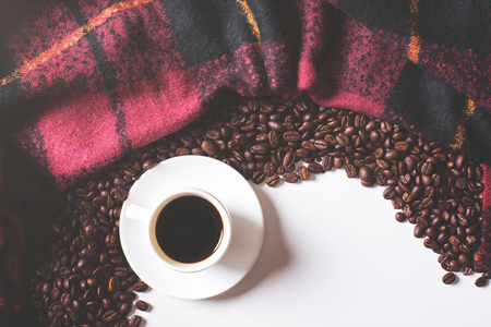 Top view of coffee cup, beans and checkered plaid. Leisure concept Stock Photo