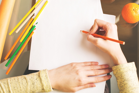 notepaper: Close up of girls hands drawing on paper sheets placed on glass desk with colorful supplies and other items. Art concept Stock Photo