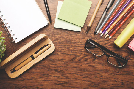 close up: Top view of wooden desktop with colorful supplies, other items and copy space Stock Photo