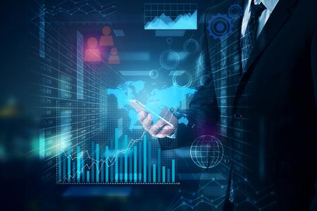 Zakenman die cellphone met abstracte blauwe bedrijfsgrafieken en pictogrammen gebruiken. Technologie concept Stockfoto