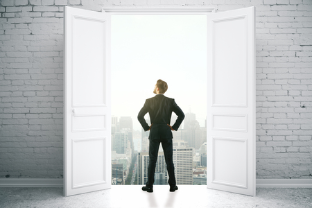looking at view: Back view of young businessman in brick interior looking out of open door with city view. Success concept. 3D Rendering