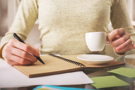 study: Close up of girls hands writing in spiral notepad placed on office desktop with coffee cup, supplies and other items. Young writerauthorartist Stock Photo