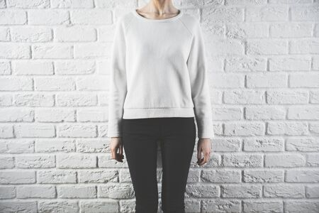 woman white shirt: Front view of young woman in casual sweater. Retail concept. White brick wall background