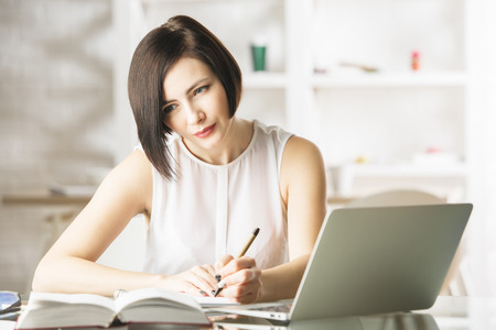 study: Portrait of beautiful young european lady doing paperwork and using laptop in modern office. She is working on project