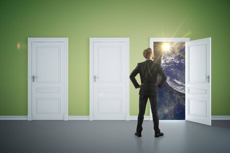 looking at view: Back view of young businessman in green interior looking out of open door with space view. Success concept. 3D Rendering Stock Photo