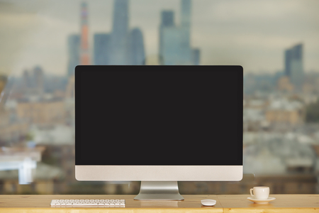 screen: Front view of hipster desktop with empty computer display, keyboard, coffee cup and other items on blurry city background. Mock up Stock Photo