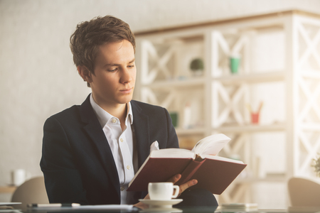 work: Attractive young european guy drinking coffee and reading book at workplacein modern office. Education concept Stock Photo