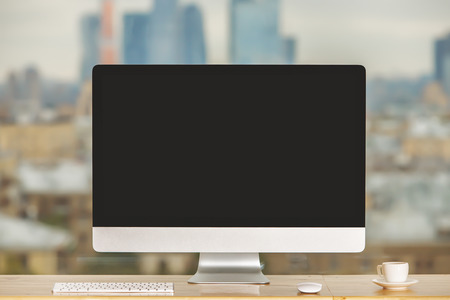 cup: Front view of windowsill desktop with empty computer display, keyboard, coffee cup and other items on blurry city background. Mock up Stock Photo