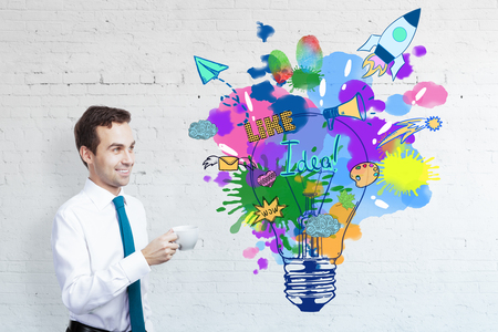 cup: HAppy european businessman drinking coffee on brick background with bright creative lamp sketch. Innovation concept
