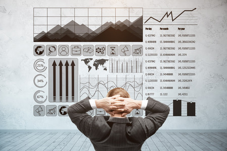 screen: Back view of relaxing young businessman looking at concrete wall with business charts. Finance concept Stock Photo