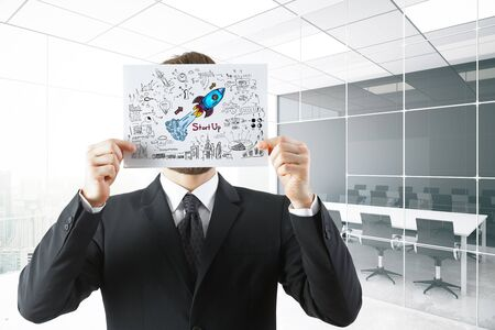 work: Young businessman covering face with rocket sketch drawn on paper sheet. Modern conference room background. Start up concept. 3D Rendering Stock Photo