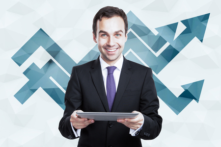 business people: Cheerful businessman using tablet on polygonal background with upward chart arrows. Success concept