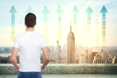 looking at view: Back view of young businessman on rooftop looking at New York city with upward chart arrows. Forward concept Stock Photo