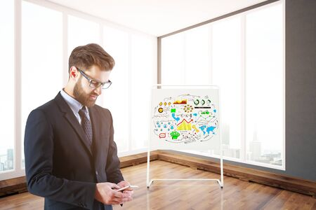 using smartphone: Side view of young businessman using smartphone in bright interior with business sketch on whiteboard stand and city view. 3D Rendering