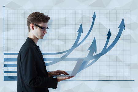Thoughtful young businessman using laptop on polygonal background with upward chart arrows. Financial growth concept Stock Photo
