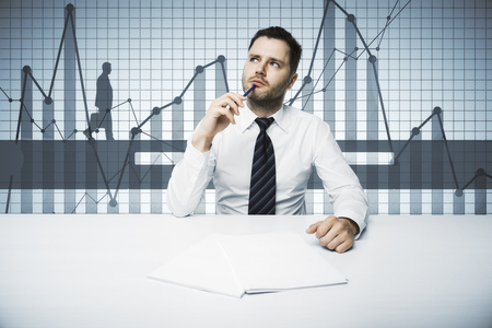 businessman pondering documents: Thoughtful young businessman doing paperwork at workplace with abstract business chart. Finance concept