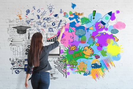 Back view of young woman drawing colorful sketch on brick wall. Creative and analytical thinking concept