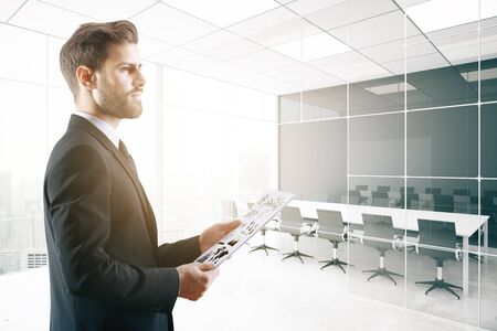 working office: Side view of young businessman holding document in bright conference room with city view. Young executive waiting for meeting. 3D Rendering