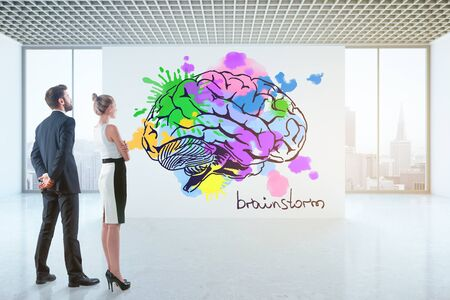 looking at view: Thoughtful young businesspeople looking at drawn colorful brain in bright concrete interior with city view. Brainstorming concept. 3D Rendering