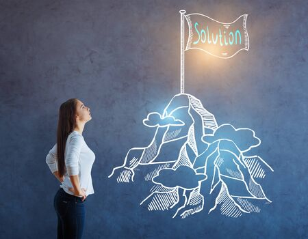 looking at view: Side view of young woman looking up to drawn illuminated mountain on concrete background. Leadership concept