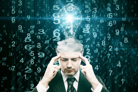 image: Abstract image of pensive young businessman with light bulb on abstract dark background with numbers. Genius concept