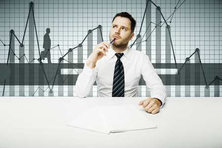 Thoughtful young businessman doing paperwork at workplace with abstract business chart. Success concept