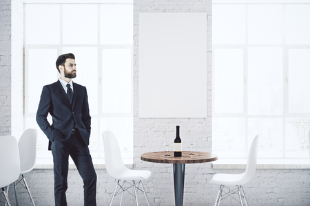 round chairs: Young businessman in bright white cafe interior with city view, wine on table and empty poster. Mock up, 3D Rendering