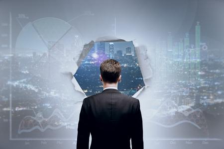Vista posterior del joven empresario mirando a la ciudad a través del agujero en la pared abstracta con gráficos de negocios. Concepto de la visión Foto de archivo - 80426007