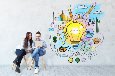 Attractive young european man and woman sitting on chairs and using tablet on concrete background with business sketch. Technology concept Archivio Fotografico