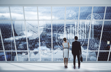 looking at view: Back view of young businessman and woman looking at city with digital business charts through panoramic windows. Teamwork concept. 3D Rendering Stock Photo