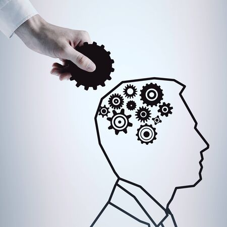 Hand putting cogwheels into drawn mans head on light background. Strategy concept Stock Photo