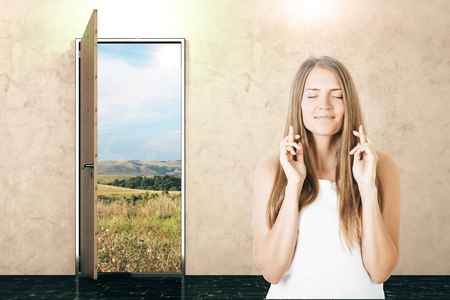 unfurnished: Open door with field view and young woman crossing fingers in concrete interior. Opportunity concept
