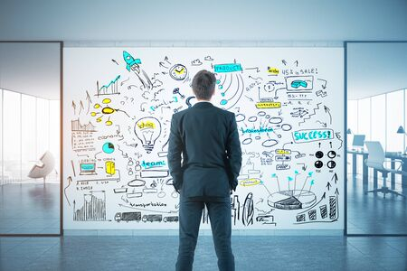 modern interior: Back view of young businessman looking at colorful business sketch in modern interior with workplace and city view. Solution concept. 3D Rendering Stock Photo