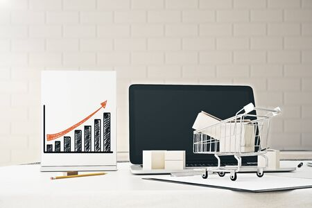 sheet of paper: Close up of blank laptop, shopping cart and business chart on poster. Brick wall background. Growth concept. 3D Rendering