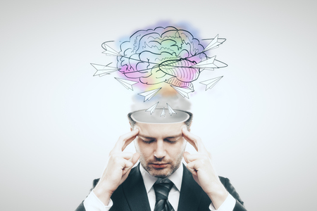 Pensive businessman with abstract brain sketch on light background. Creative thinking concept Stok Fotoğraf