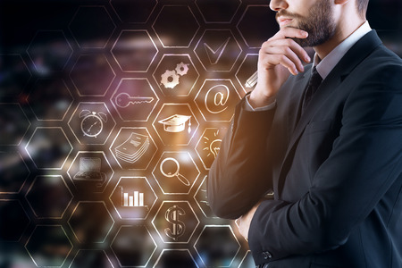 Side view of thoughtful young businessman in suit standing on blurry night city background with business icons in cells. Tech concept. Double exposure Stockfoto