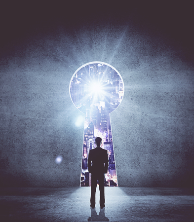 key hole: Back view of young businessman standing in concrete interior with keyhole opening and illuminated night city view. Accessibility concept. 3D Rendering Stock Photo